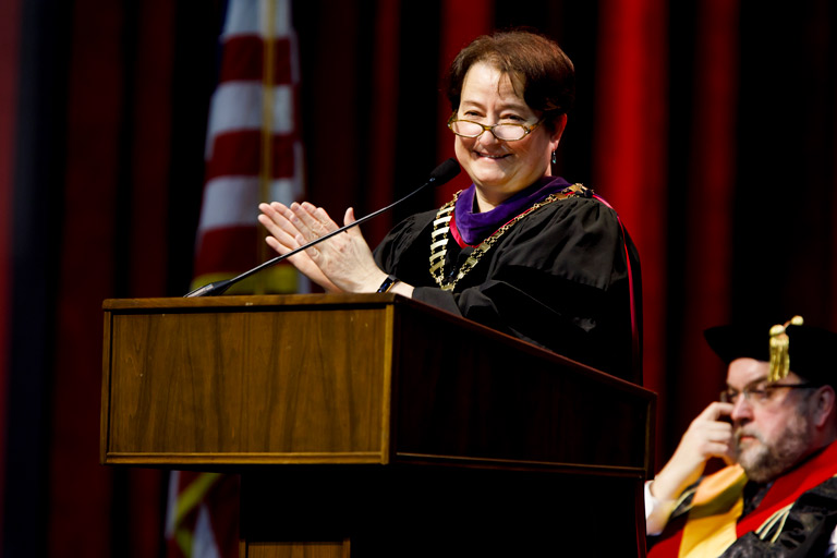 IU provost Lauren Robel smiles and applauds while standing at a lectern.