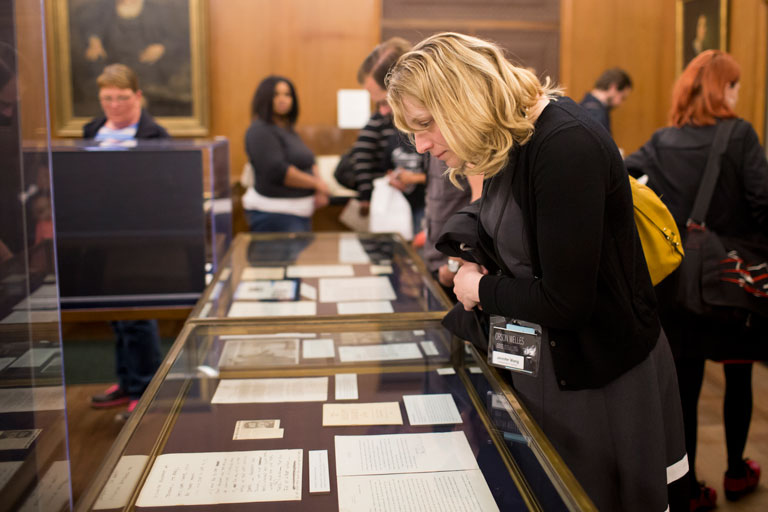 A woman looks at documents on display in a glass case at the Lilly Library.