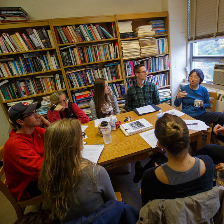 Students sit around a table and listen to a faculty member.
