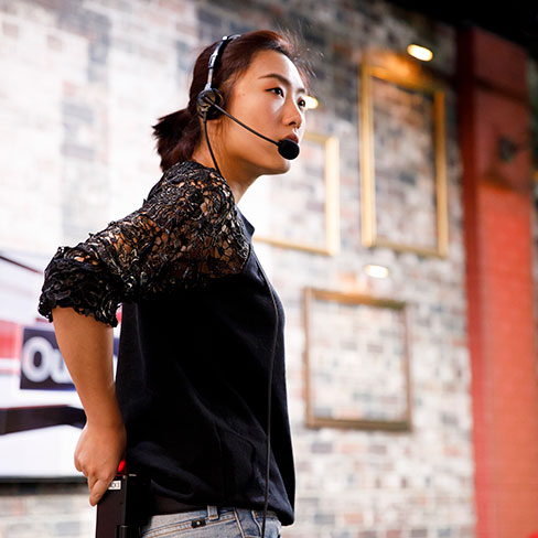 A student wearing a wireless headset and microphone stands in front of a brick wall.