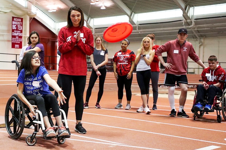 Onlookers watch as a child in a wheelchair throws a frisbee.
