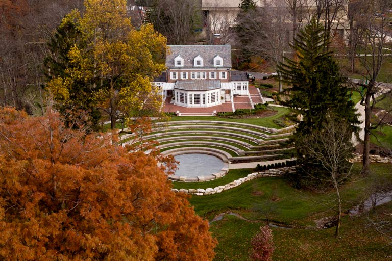 An aerial view of Bryan House and the Conrad Prebys Amphitheater surrounded by fall foliage
