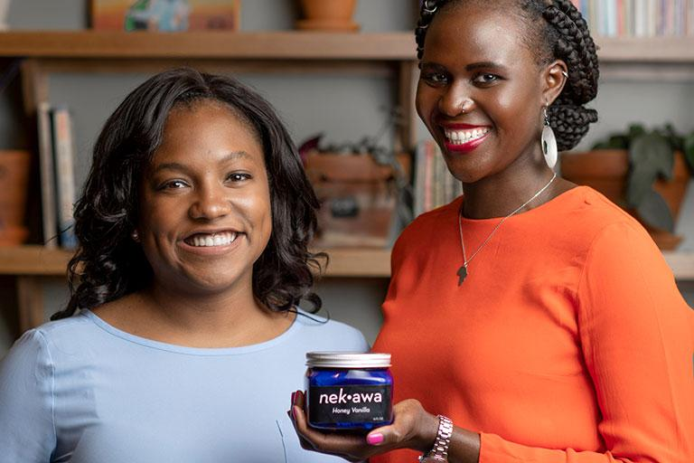 Chelsea Trotter, left, and Awa Diaw hold a jar of their product