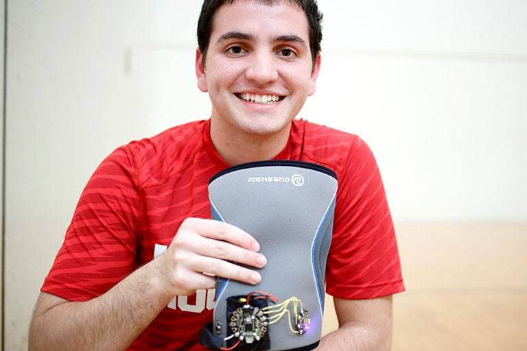 Shayan Khokhar holds MuscleMemory, the knee brace he created
