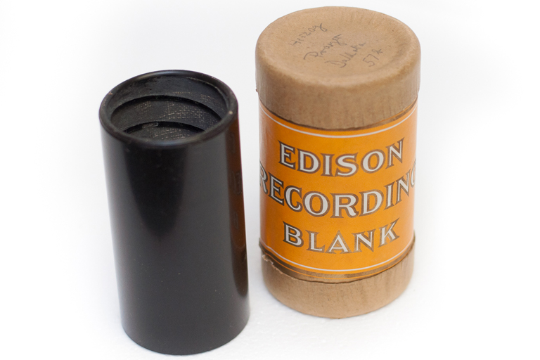 A wax cylinder with a recording sits next to its container, marked Edison Recording Blank.