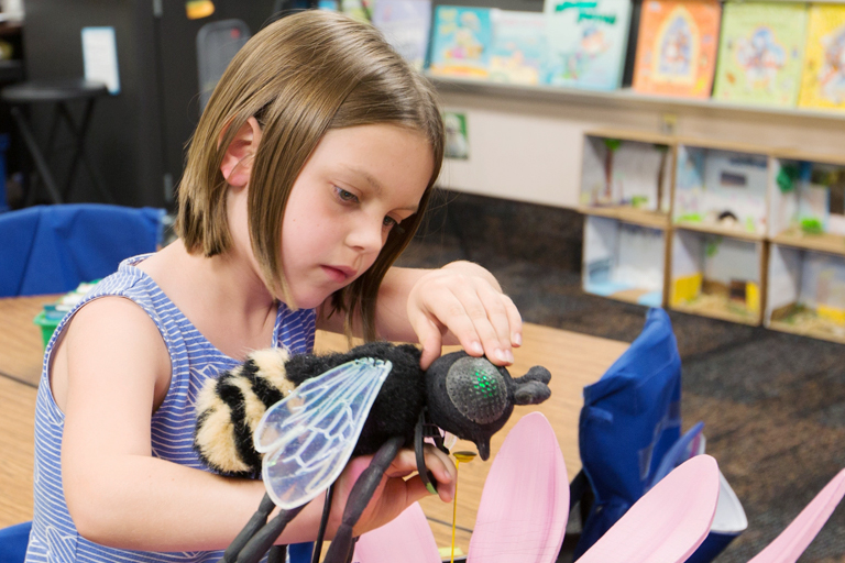 A young girl examines a plush model of a bee.