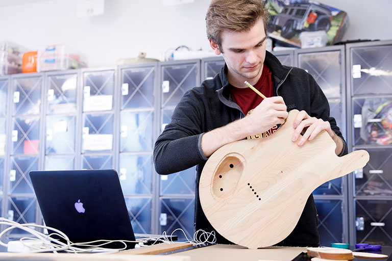 A student marks on a wooden guitar body in a makerspace.