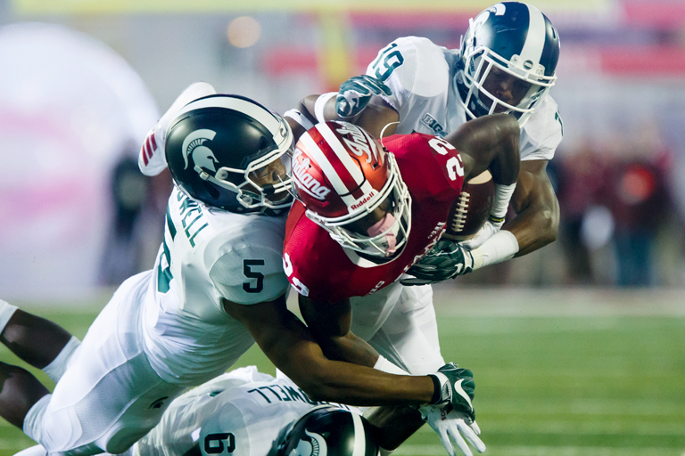 An IU football player is tackled by two Michigan State players.