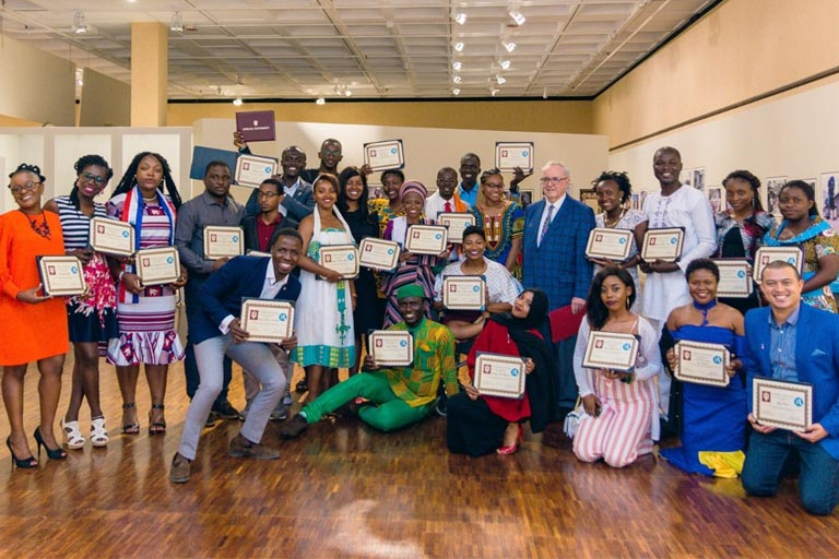 A group of young African leaders holding framed certificates