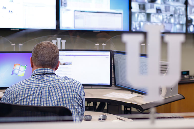 A man works at a computer, in front of several screens.