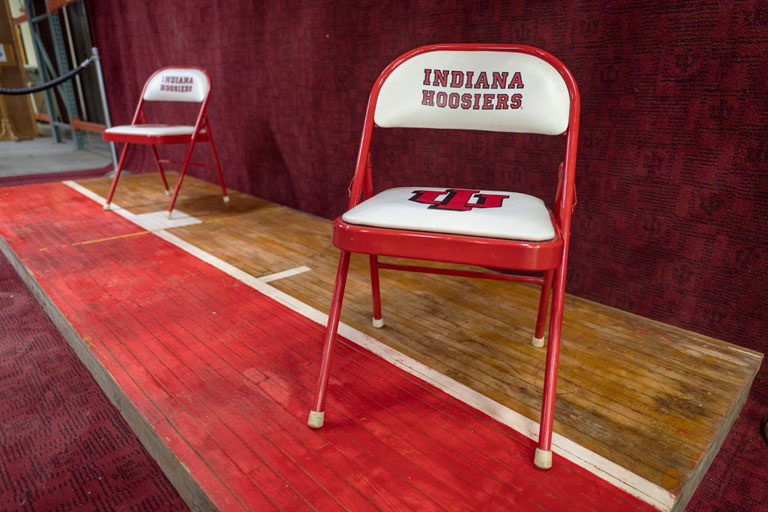 Folding chairs printed with Indiana Hoosiers are displayed on a vintage floorboard.