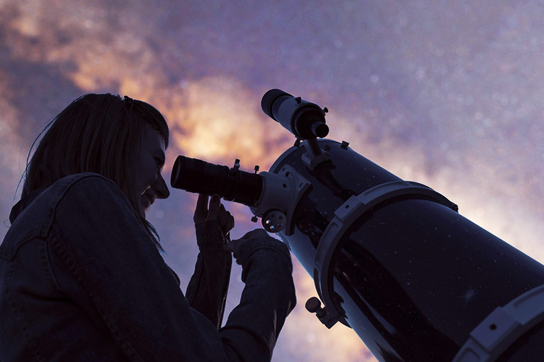 A woman looks through a telescope.