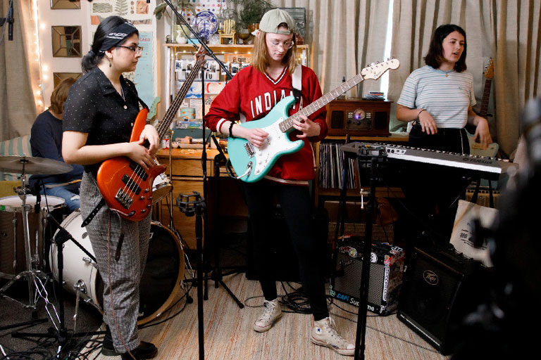 A drummer, two guitarists, and a keyboard player perform a dorm room concert.