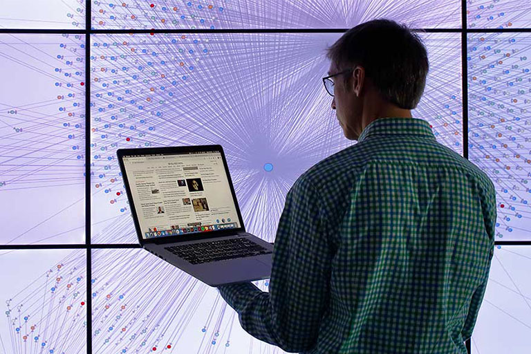 A man looks at a laptop in front of a large video screen.