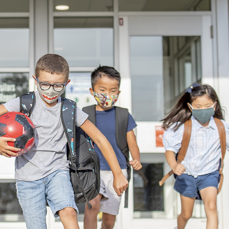 Three children run while wearing backpacks and masks.