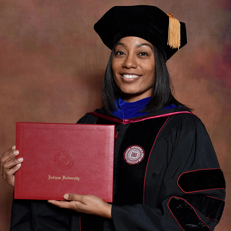 A graduate in her cap and gown holds an Indiana University diploma cover.