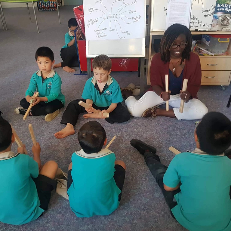 An IU student plays with wooden sticks with children in New Zealand.