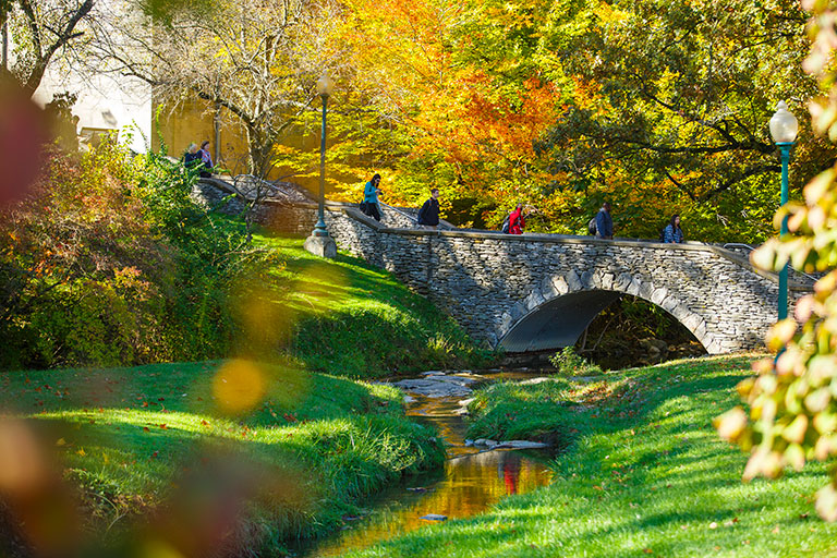 Students cross a stone bridge over the Jordan River on a sunny autumn day.