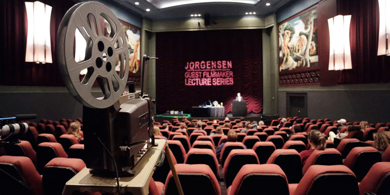 Empty seats in the iU Cinema with a film projector in the foreground with the words Jorgenson Lecture Series on the screen.