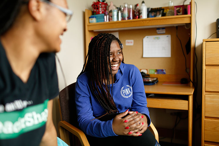 Two young women laugh in a dorm room.