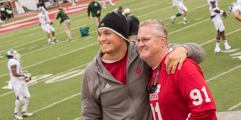 A young man and an older man stand on the IU football field smiling with players in the background.