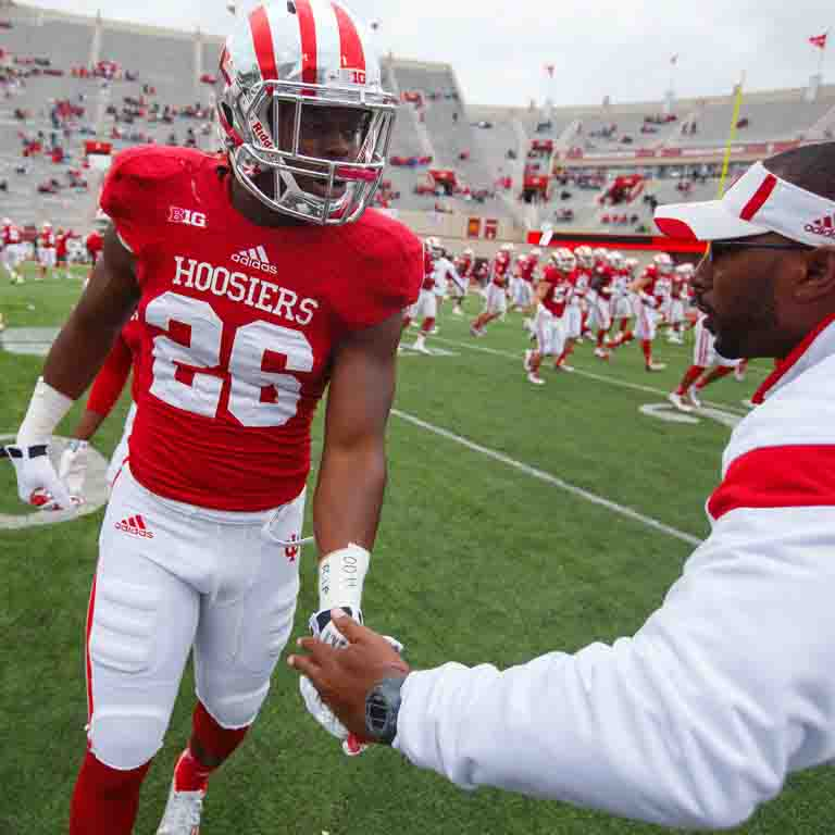 An IU football player talks with a coach on the sideline.