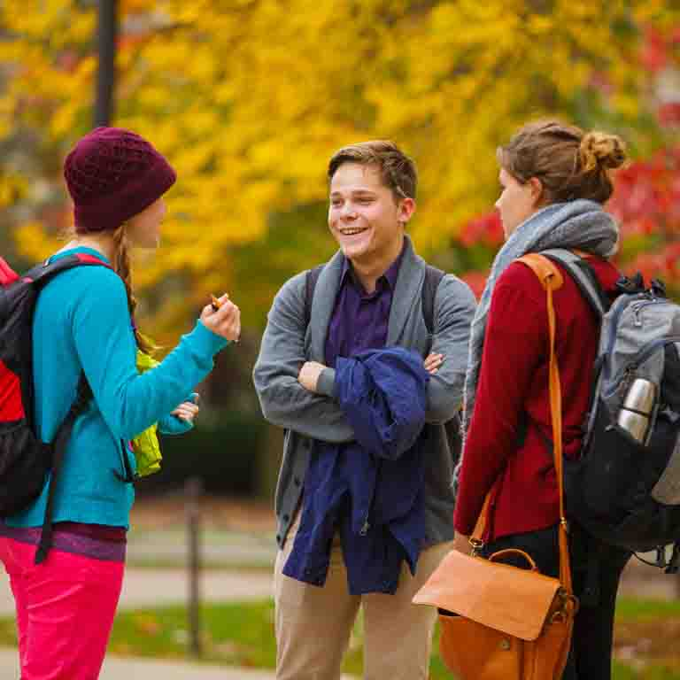Three students talk on a fall day.