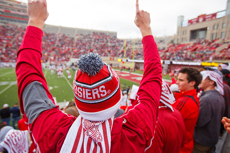 "A student wearing a red and white knit cap gives a ""We're number one"" hand sign at a game."
