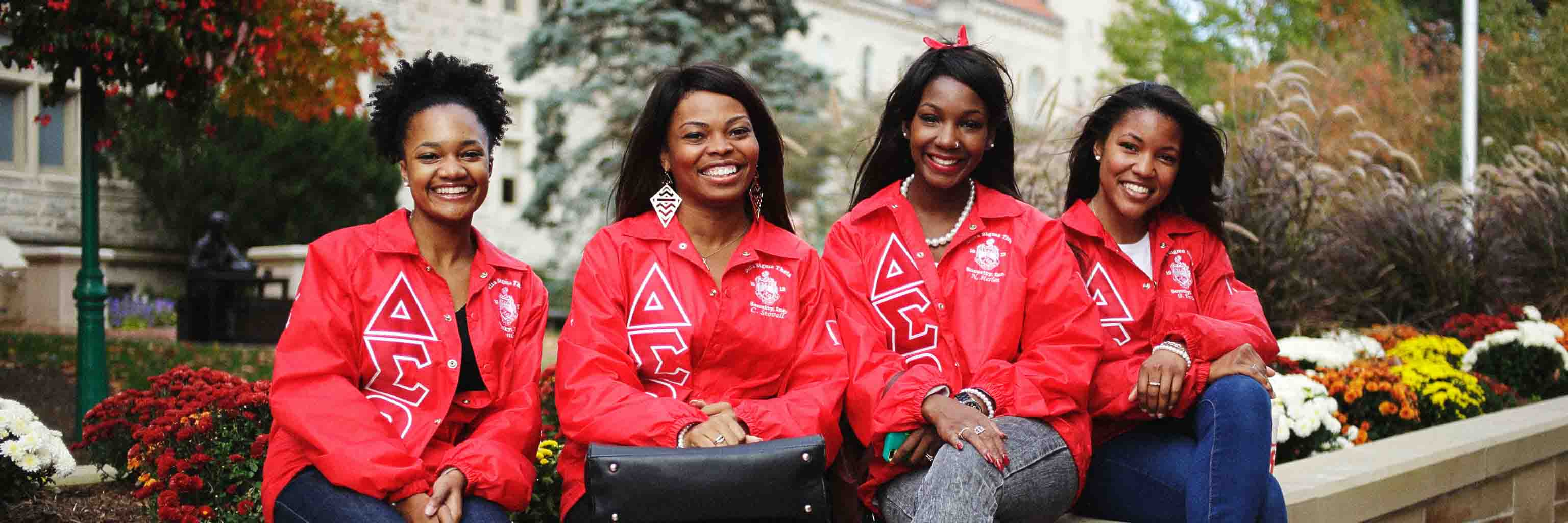 Four African American women in sorority jackets sit smiling on a bench.