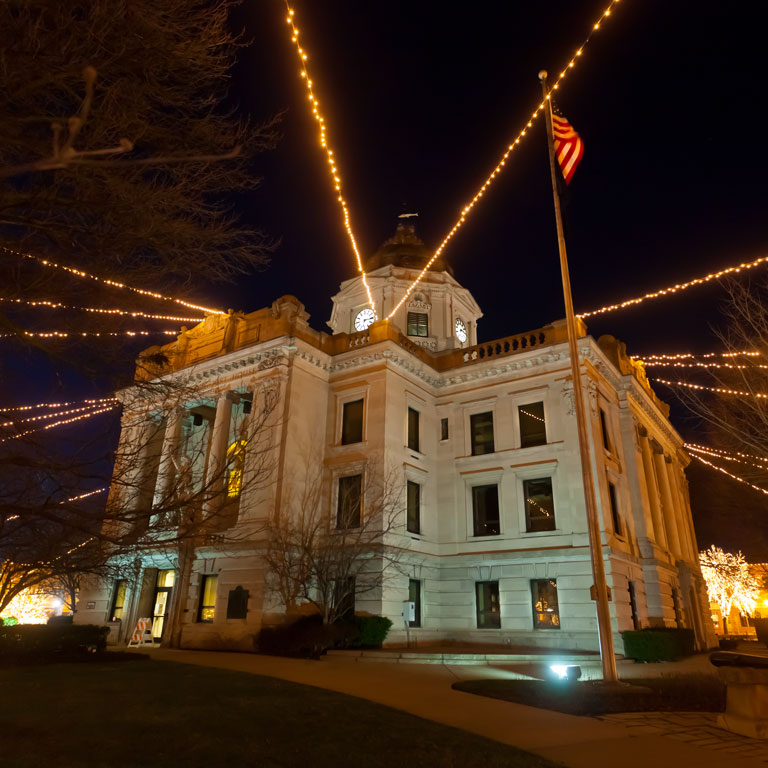 Holiday lights extending from the courthouse at night.