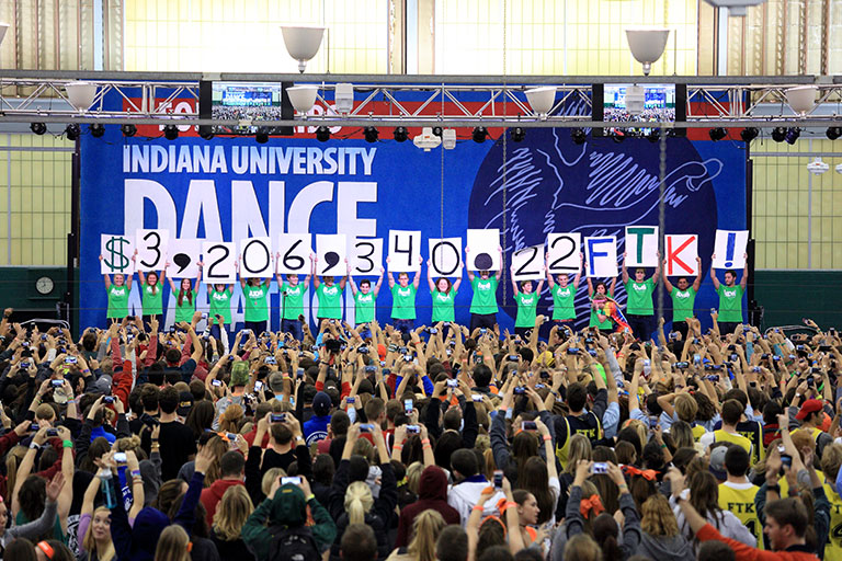 IU Dance Marathon participants hold up signs indicating they raised $3,206,340 for Riley Hospital.
