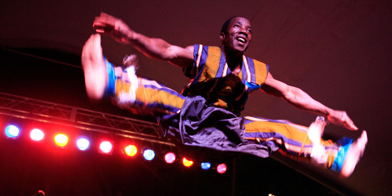 A man in colorful costume does a split toe-touch jump.