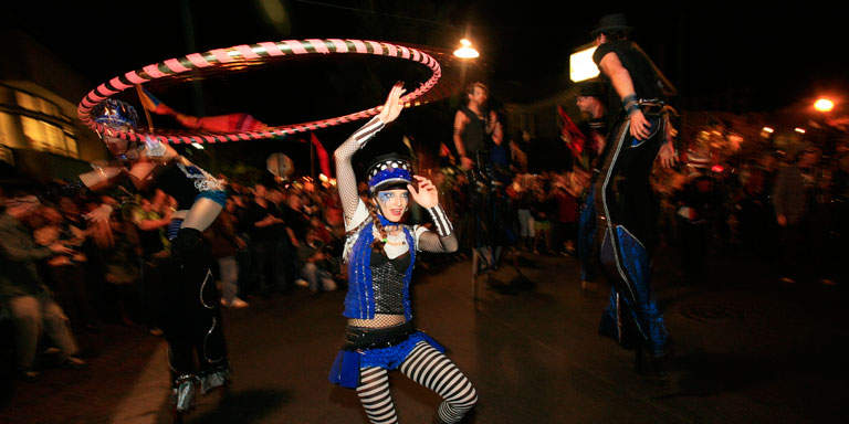 A woman in a costume twirls a hula hoop above her head as other costumed performers on stilts walk nearby.