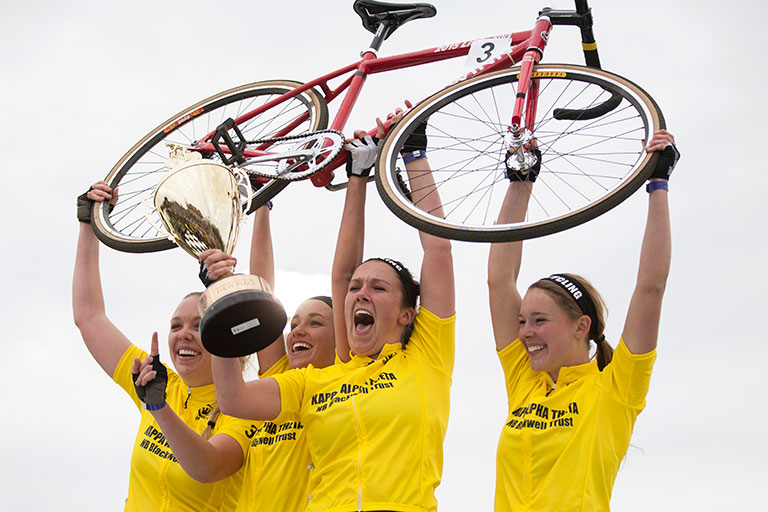 A winning women's Little 500 team holds a bike and trophy above their heads.