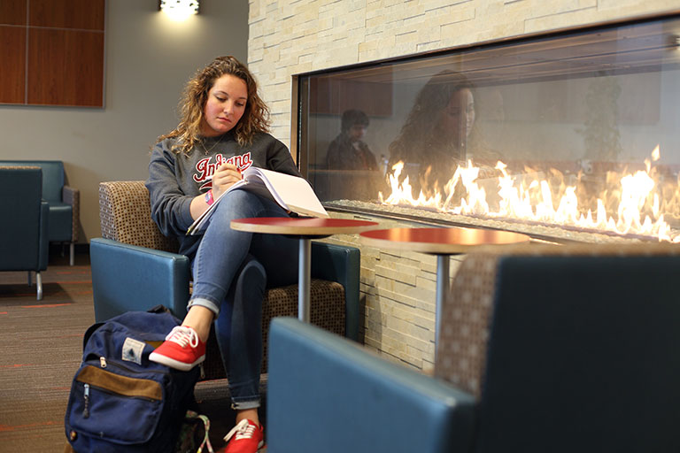A young woman studies next to a fireplace.