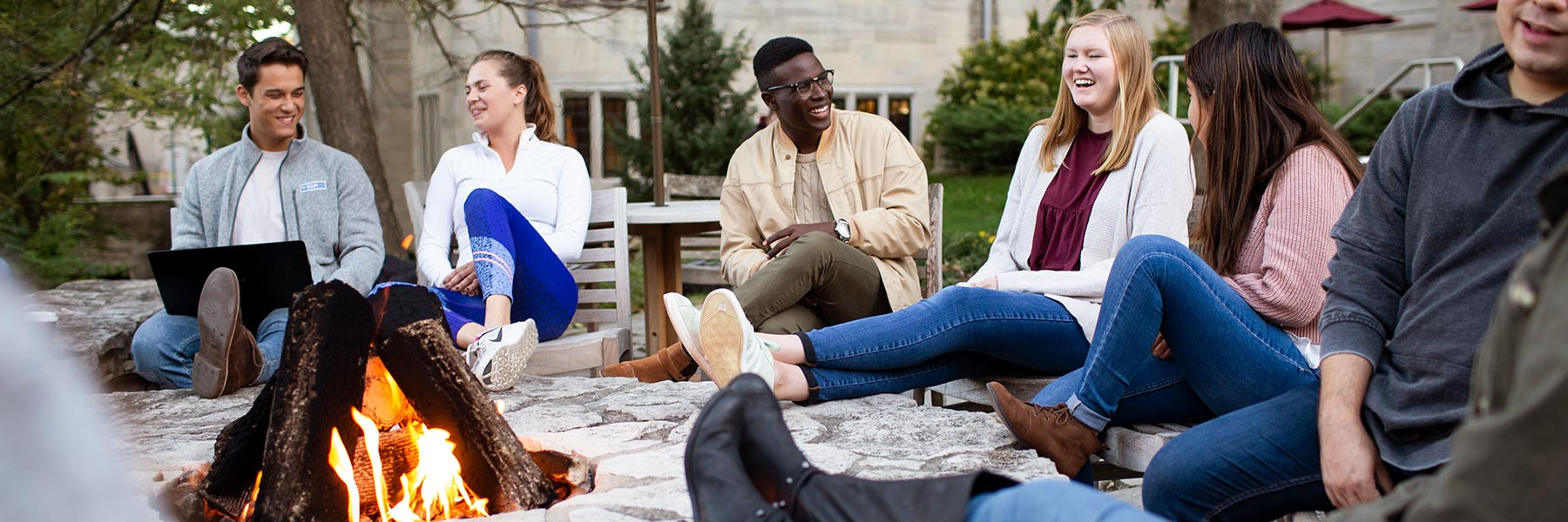 Students sitting around a fire pit